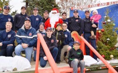 Caption: Lockwood Fire Chief John Staley posing with Santa along with his crew and volunteers at Canary and Bluebird in Lockwood during one of the visits. It takes a crew of about a dozen people to prep, help, take down and then move the Santa set from location to location. (Photo by Jonathan McNiven)