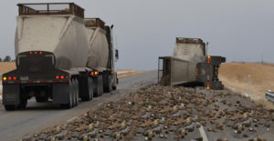 A loaded sugar beet truck slowly passes another driver who's sugar beet truck turned over Sunday morning on I-94 at mile marker 4. Highway Patrol Trooper reported the accident was caused due to the driver's fatigue. The accident was called into dispatch at 6:32am. It took crews a couple hours to remove all the remaining sugar beets in the trailer as well as pick up all the remaining beets alongside the Interstate. (Image by Jonathan McNiven)