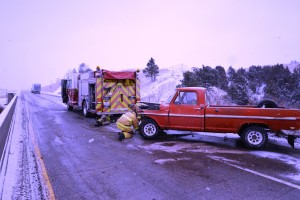 Damaged 1968 F-100 pickup truck with frontend damage due to slippery road conditions on Wednesday Nov. 25th on Yellowstone River bridge on Interstate 90. Fire fighters are hooking to the pickup in order to pull it off the interstate in order for traffic to start moving again on the Interstate.