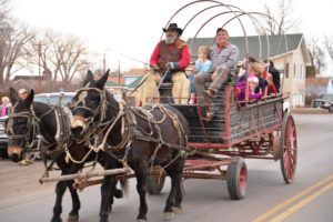 Happy Pappy, front left, of Western Romance Company giving free mule-drawn wagon rides to Keith Rauch, front right, of Shepherd, and his family last year at the Huntley Christmas Stroll. Free wagon rides will be available in Huntley from noon – 4 p.m. Saturday, Dec. 19, weather permitting. (Jonathan McNiven Photo)